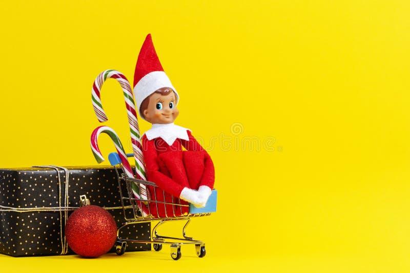 Mini carrinho de compras com pequenos brinquedos Santa elf e canas doces, bola bauble de decoração de Natal e caixa de presentes  imagens de stock