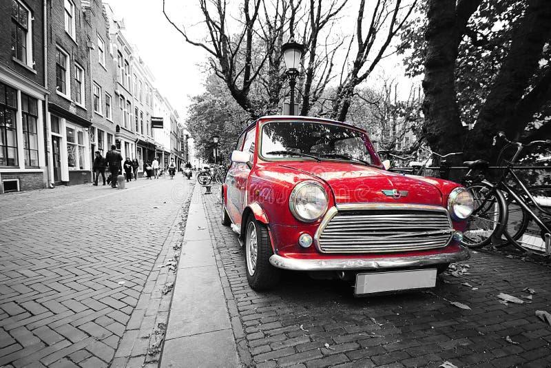 Mini carro clássico preto e branco vermelho do tanoeiro no cartão de holland fotografia de stock royalty free
