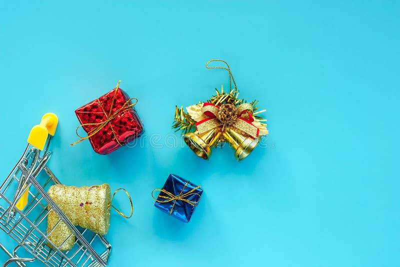 Mini carro de la compra con los ornamentos de Navidad y decoración en vagos azules foto de archivo libre de regalías