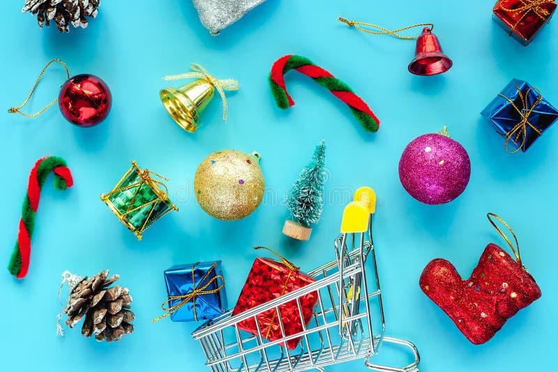 Mini carro de la compra con los ornamentos de Navidad y decoración en vagos azules fotos de archivo libres de regalías