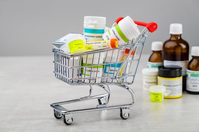 Mini carro de la compra por completo de remedios homeopáticos Concepto de comprar drogas homeopáticas foto de archivo libre de regalías