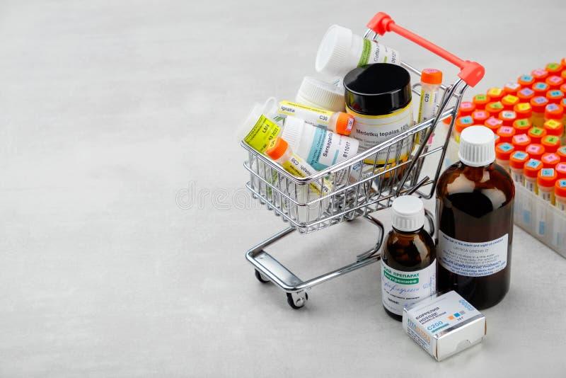 Mini carro de la compra por completo de remedios homeopáticos y del equipo de primeros auxilios con diversa preparación homeopáti foto de archivo libre de regalías