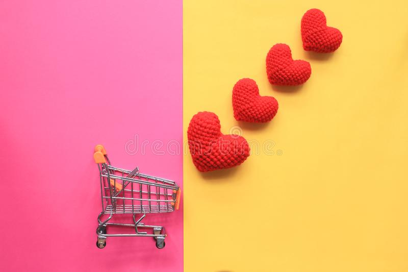 Mini carro de la compra y corazón hecho a mano rojo del ganchillo en el fondo amarillo y rosado para día de San Valentín fotografía de archivo libre de regalías