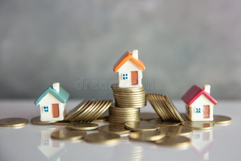 Mini casa en la pila de monedas, de dinero y de casa, de dinero de la hipoteca, de los ahorros para la casa de la compra y de pr? imagen de archivo libre de regalías