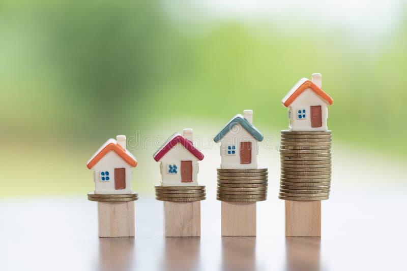 Mini casa na pilha de moedas, conceito da propriedade do investimento, do risco de investimento e da incerteza no mercado imobili imagens de stock