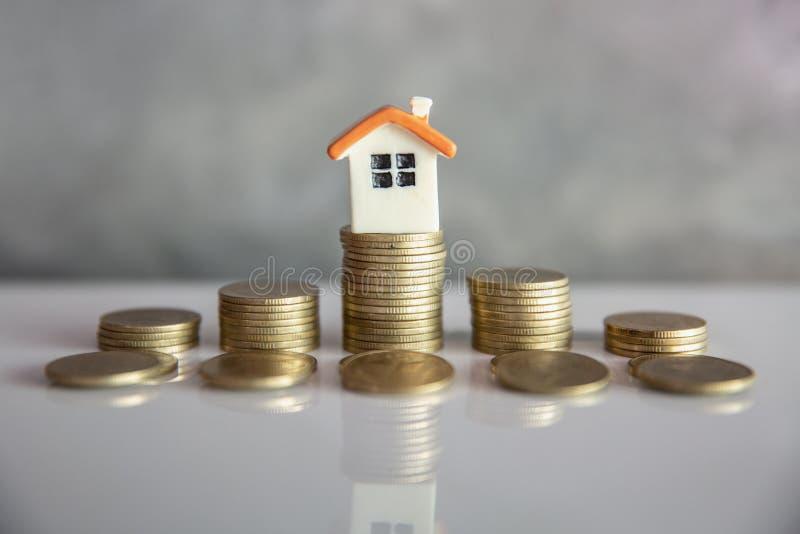 Mini casa na pilha de moedas Conceito da propriedade e da gestão de riscos do investimento foto de stock