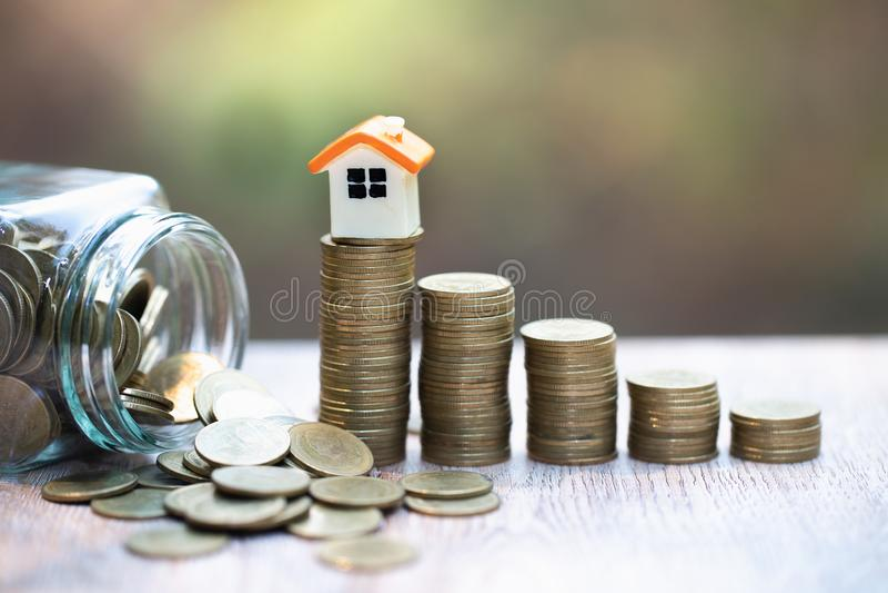 Mini casa na pilha de moedas Conceito da propriedade e da gest?o de riscos do investimento imagem de stock