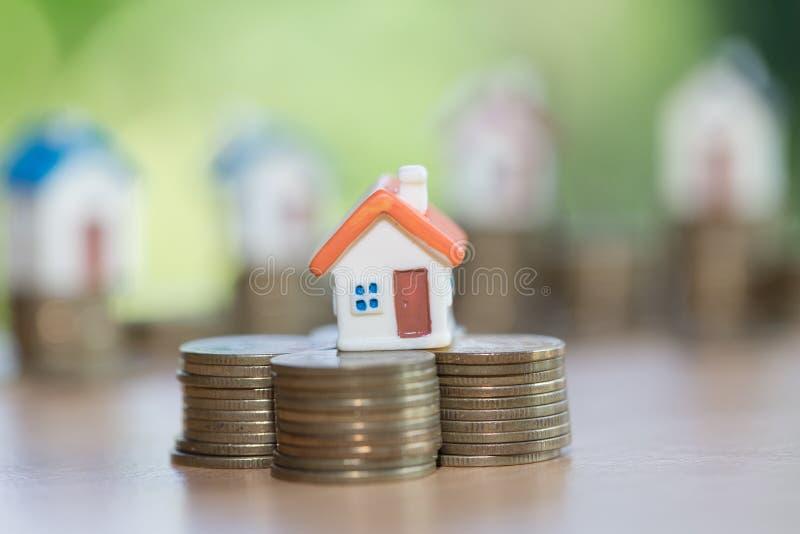 A mini casa na pilha de moedas, dinheiro e casa, bens imobiliários investe fotos de stock