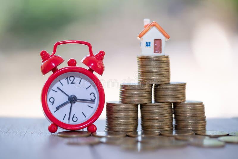 Mini casa na pilha de moedas, de dinheiro e de casa, de dinheiro da hipoteca, das economias para a casa da compra e de empréstimo fotografia de stock royalty free