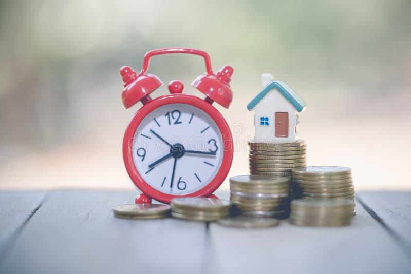 Mini casa na pilha de moedas, de dinheiro e de casa, de dinheiro da hipoteca, das economias para a casa da compra e de empréstimo foto de stock