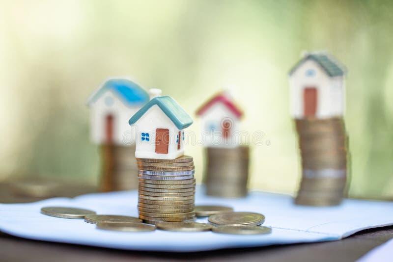 A mini casa na pilha de moedas, de dinheiro e de casa, organismos de investimento imobiliário, salvar o dinheiro com moeda da pil imagem de stock