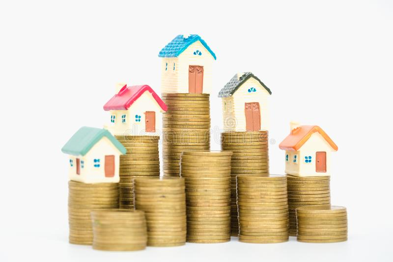 Mini casa sulla pila di monete, isolata su fondo bianco, concetto della proprietà di investimento immagini stock