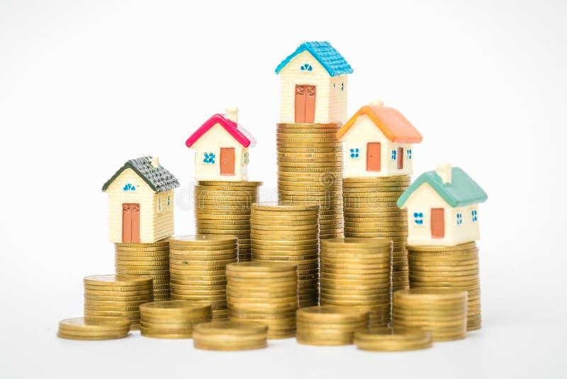 Mini casa sulla pila di monete, isolata su fondo bianco, concetto della propriet? di investimento fotografia stock libera da diritti