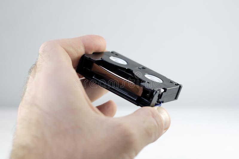 Mini cassettes de DV en una mano fotos de archivo libres de regalías