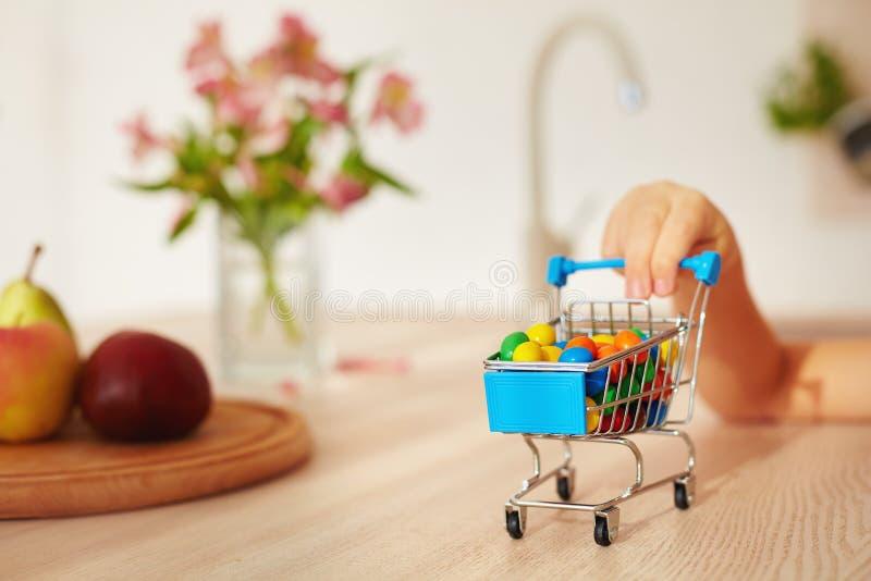 Mini chariot à achats complètement des sucreries sur le bureau de cuisine photo libre de droits