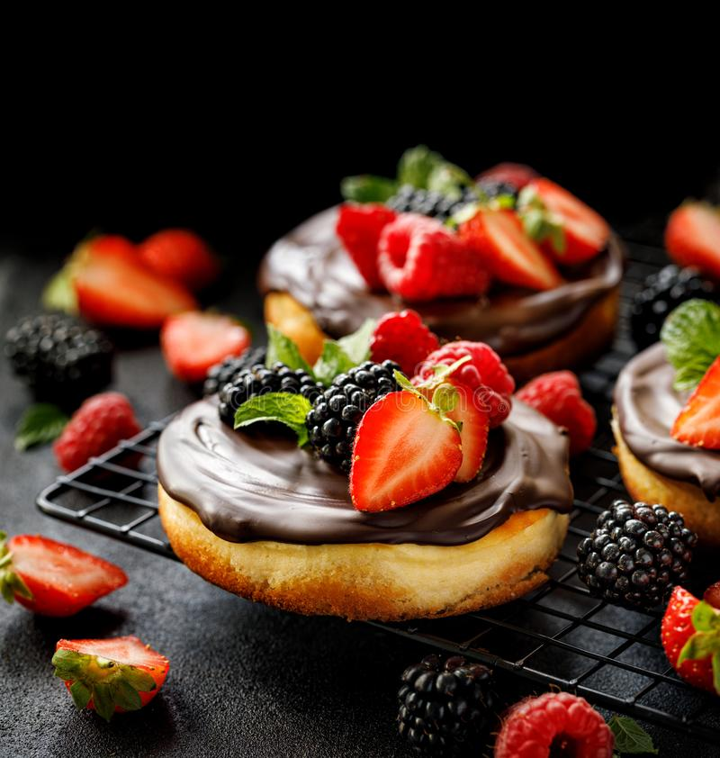 Mini cheesecake covered with chocolate with the addition of fresh berry fruits: blackberry, raspberry, strawberry, cherry and mint royalty free stock images