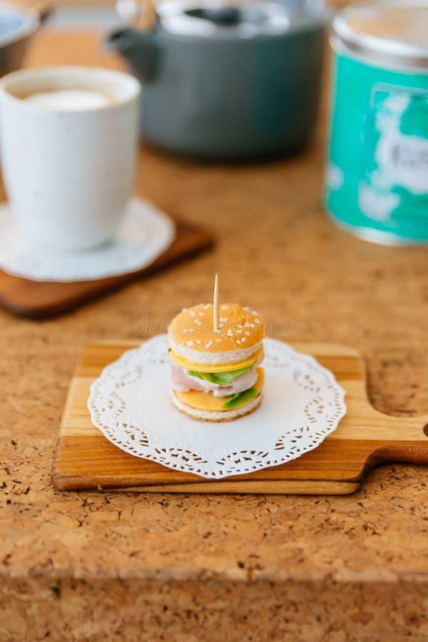 Mini Chicken Burger na placa de desbastamento de madeira com o copo e a caneca de chá do borrão no fundo imagem de stock