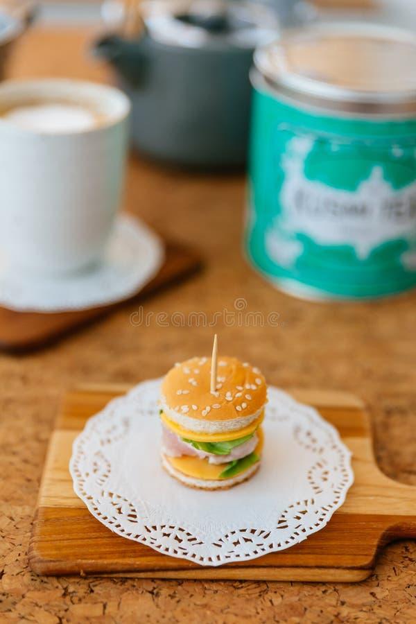 Mini Chicken Burger na placa de desbastamento de madeira com o copo e a caneca de chá do borrão no fundo fotos de stock royalty free