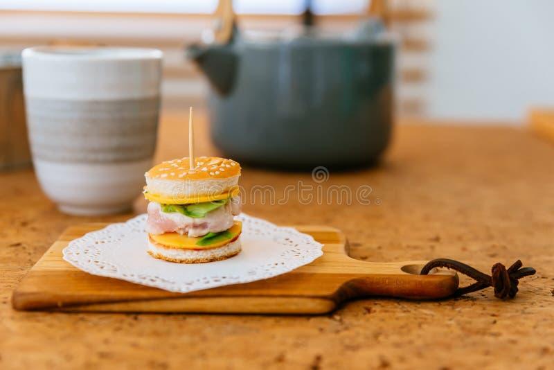 Mini Chicken Burger na placa de desbastamento de madeira com o copo e a caneca de chá do borrão no fundo imagens de stock
