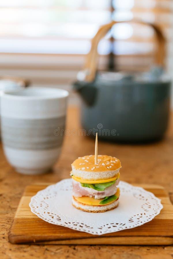 Mini Chicken Burger na placa de desbastamento de madeira com o copo e a caneca de chá do borrão no fundo imagens de stock royalty free