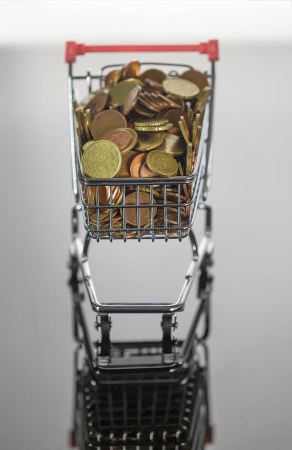 Mini Chrome Shopping Cart fylld överst med mynt arkivbilder