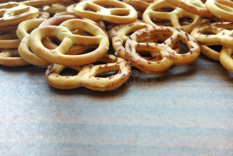 Mini ciambelline salate del cracker croccante salato sul fondo di legno della tavola immagine stock libera da diritti
