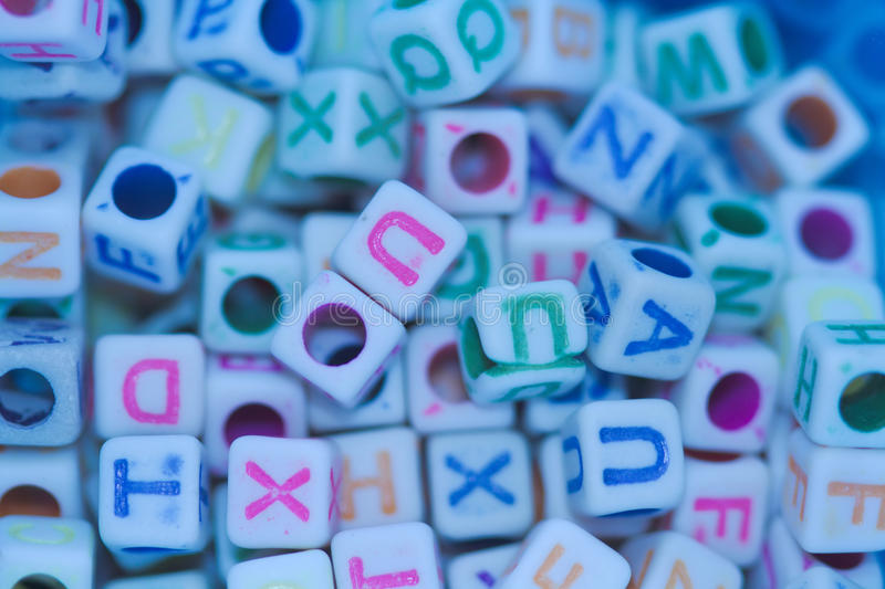 Mini coloured letter craft cubes. A macro image of a collection of mini craft cubes or beads with coloured letters on them royalty free stock photography