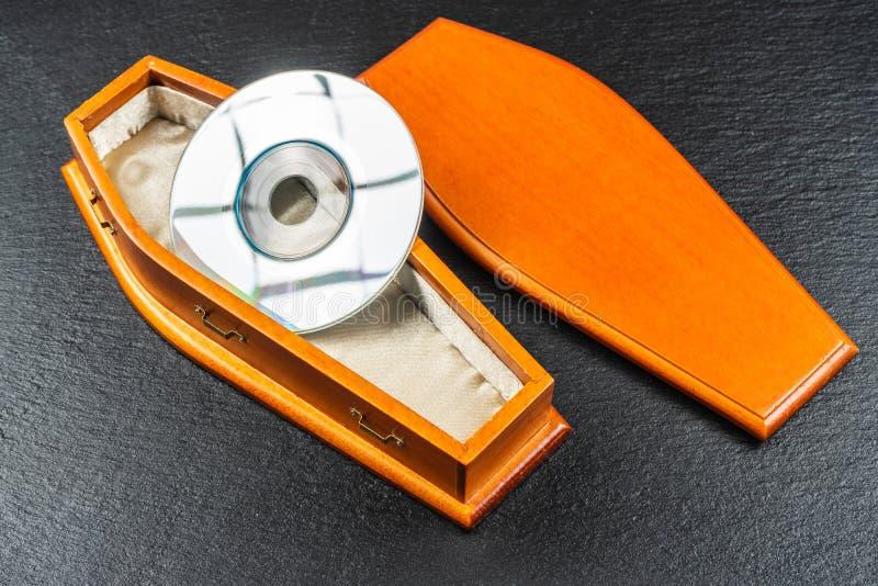 Mini compact disc or pocket compact disc in coffin.Concept.  stock photos