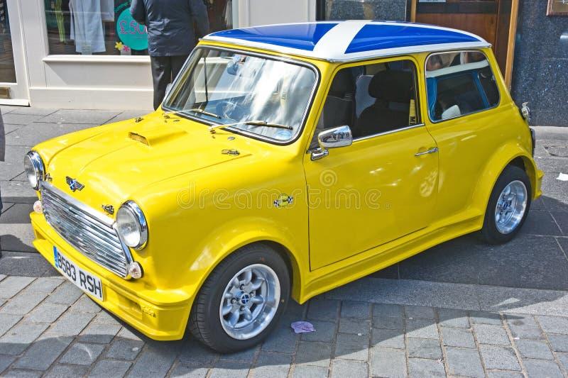 Mini Cooper amarelo com a bandeira escocesa no telhado imagens de stock