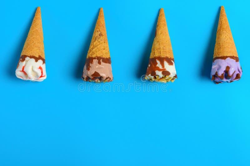 Mini cornets de crème glacée frais sur le fond bleu image libre de droits