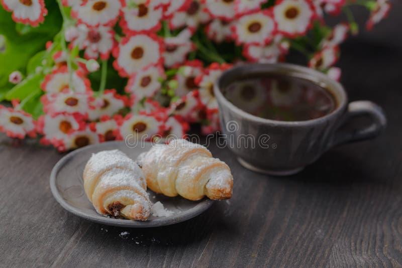 Mini croissant su una tavola di legno, bagel con una tazza di caffè su una tavola di legno, bagel su una tavola di legno fotografie stock