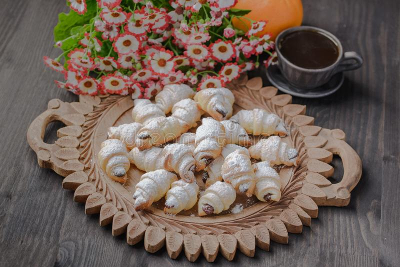 Mini croissant su una tavola di legno, bagel con una tazza di caffè su una tavola di legno, bagel su una tavola di legno fotografia stock libera da diritti