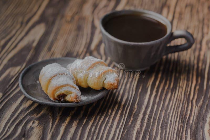 Mini croissant su una tavola di legno, bagel con una tazza di caffè su una tavola di legno, bagel su una tavola di legno immagine stock