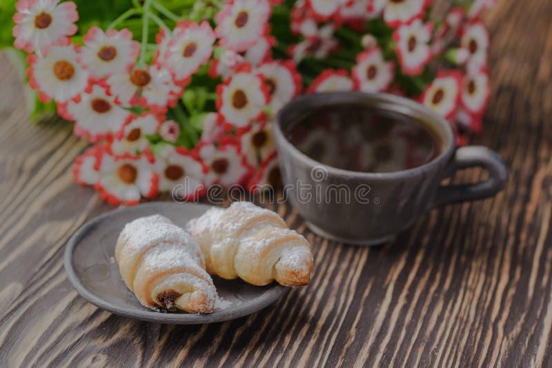 Mini cruasanes en una tabla de madera, panecillos con una taza de café en una tabla de madera, panecillos en una tabla de madera fotografía de archivo