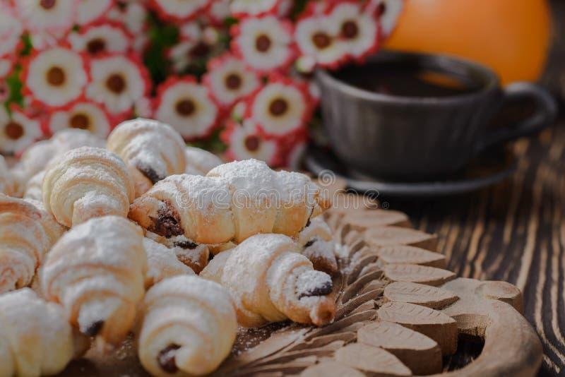 Mini cruasanes en una tabla de madera, panecillos con una taza de café en una tabla de madera, panecillos en una tabla de madera fotos de archivo libres de regalías