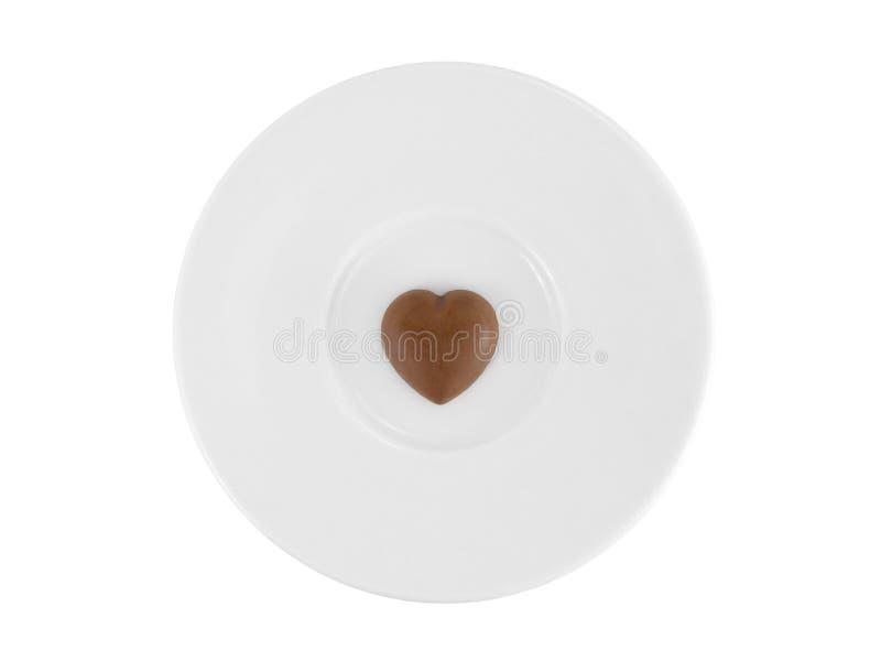 Mini dark heart shaped chocolate on white ceramic plate isolated on white background stock images