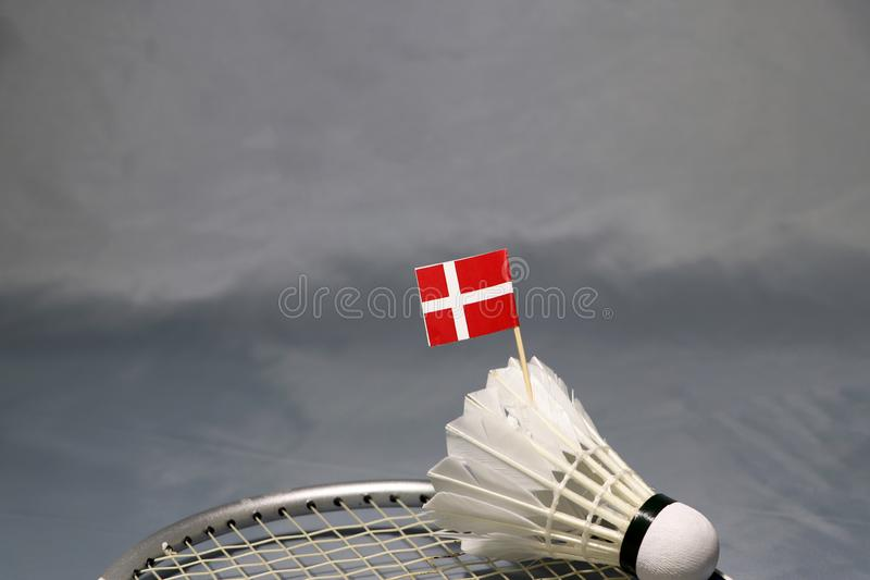 Mini Denmark flag stick on the shuttlecock put on the net of badminton racket on the grey floor. Concept of badminton sport stock images