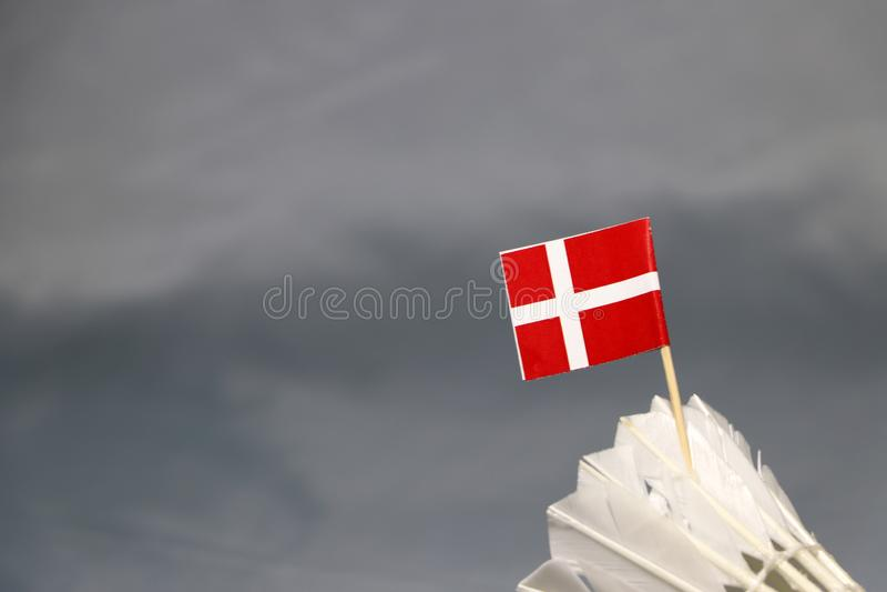 Mini Denmark flag stick on the white shuttlecock on the grey background. Concept of badminton sport royalty free stock photo