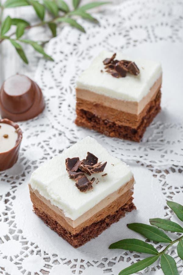 Mini dolci con cioccolata bianca, cacao e le caramelle su fondo leggero fotografia stock