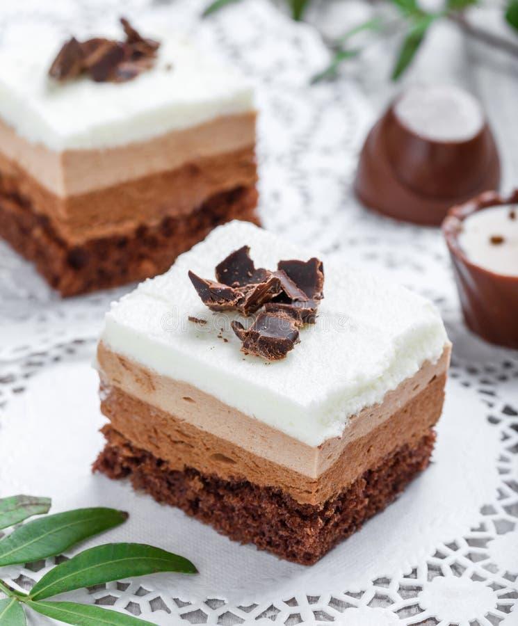 Mini dolci con cioccolata bianca, cacao e le caramelle sulla fine leggera del fondo su fotografia stock libera da diritti