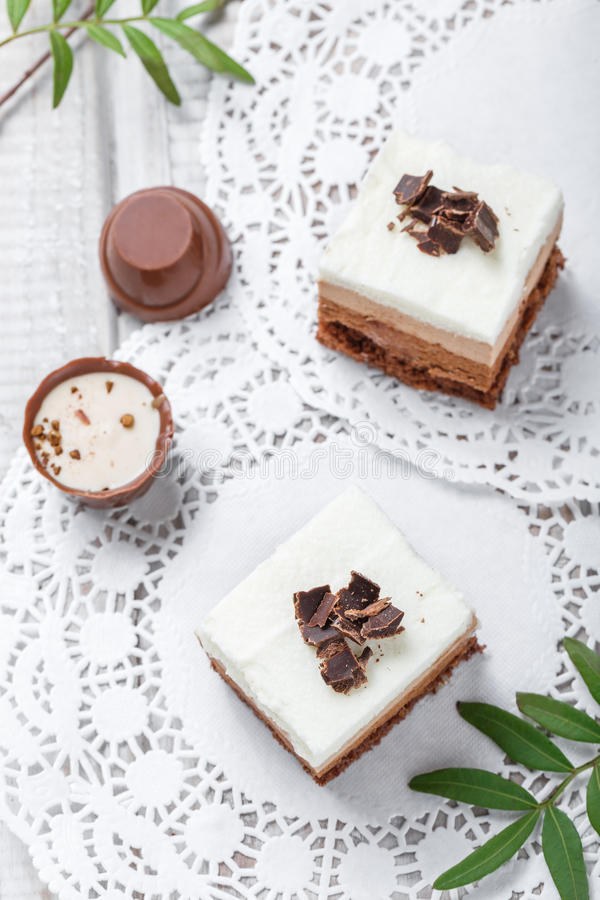 Mini dolci con cioccolata bianca, cacao e le caramelle sulla fine leggera del fondo su fotografie stock