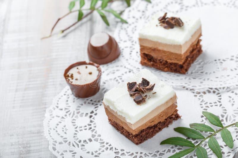 Mini dolci con cioccolata bianca, cacao e le caramelle sulla fine leggera del fondo su immagini stock libere da diritti