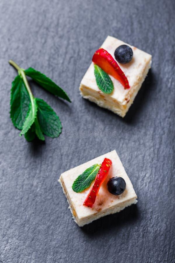 Mini dolci con la fragola ed il mirtillo sulla fine di pietra del fondo dell'ardesia su Cottura casalinga fotografia stock libera da diritti