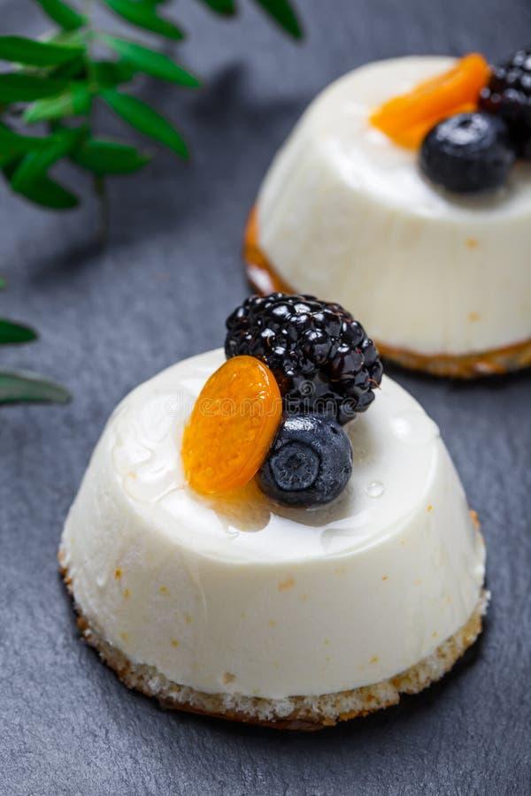 Mini dolci con le albicocche secche e le more sulla fine di pietra del fondo dell'ardesia su immagine stock