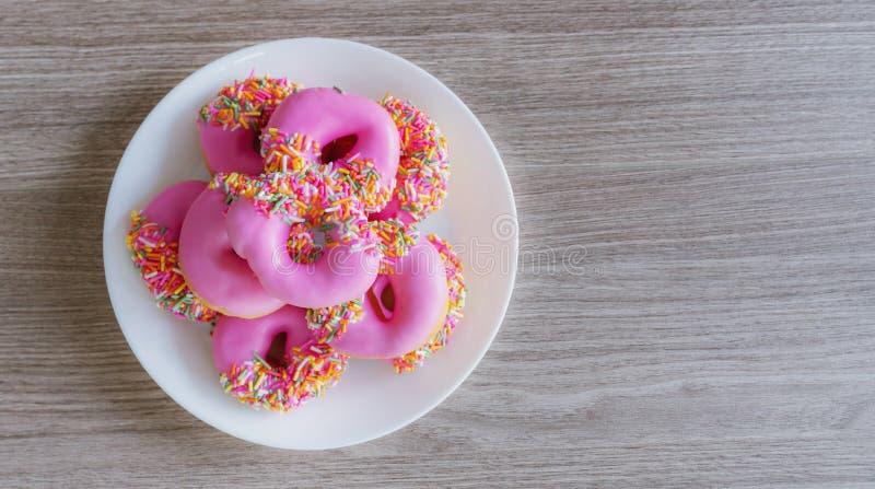 Mini donuts vitrés roses dans une assiette blanche sur une table en bois Contexte alimentaire sucré images stock