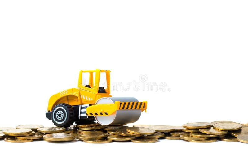 Mini Drogowego rolownika maszyna z stosem złocista moneta, odosobnionym na whi obraz royalty free