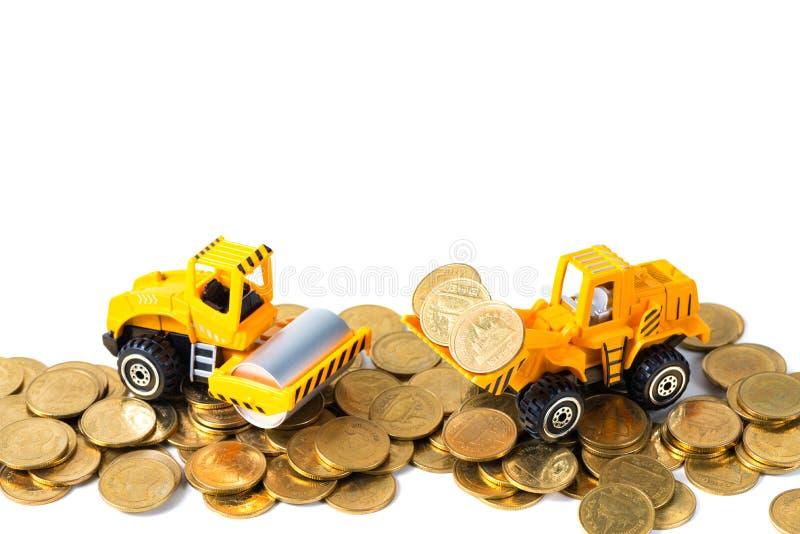 Mini Drogowego rolownika maszyna z stosem złocista moneta, odosobnionym na whi fotografia stock