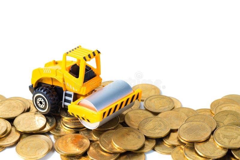 Mini Drogowego rolownika maszyna z stosem złocista moneta, odosobnionym na whi obraz stock