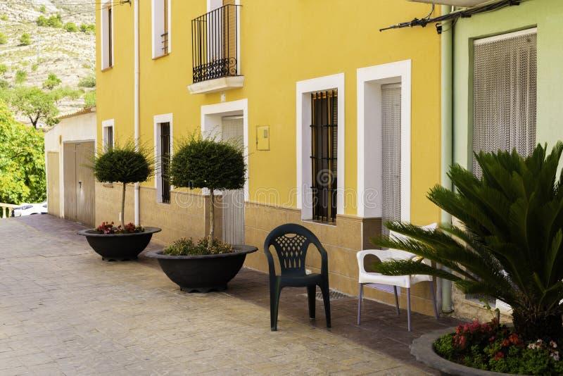 Mini drzewa w kwiatów krzesłach na wygodnej Śródziemnomorskiej ulicie w starym miasteczku Releu i garnkach, Hiszpania miejsca tar obraz royalty free