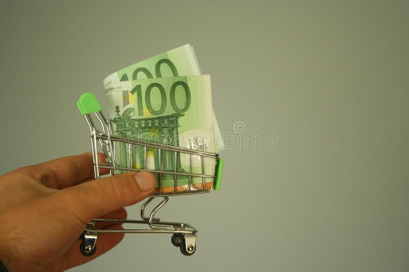 Mini dummy shopping cart in human hand with paper euro banknotes as a concept for online shopping, saving, business and making mon. A mini dummy shopping cart in stock photography